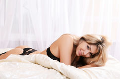 The beautiful blonde girl on bed Stock Photos