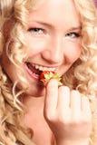 Beautiful blonde girl biting strawberry. Studio shot Stock Photo