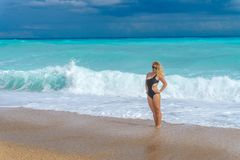 Beautiful blonde girl in a black bikini  relax on an empty Caribbean beach. With azure sea. Perfect vacation Royalty Free Stock Image