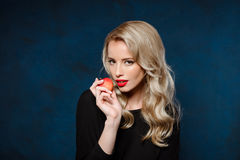 Beautiful blonde girl in black dress holding apple, looking at camera. Stock Images
