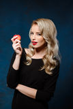 Beautiful blonde girl in black dress holding apple, looking at camera. Stock Image