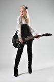 Beautiful blonde girl with black electric guitar stock photos