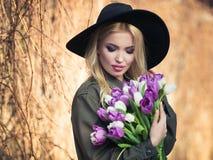 Beautiful blonde girl in a black hat is enjoying tulips bouquet. Beautiful, romantic blonde girl in a black hat is enjoying a bouquet of white and purple tulips stock photo