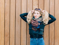 Beautiful blonde girl in black jacket posing nex to wooden wall on a sunny day and playing with her hair Royalty Free Stock Photography