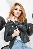 Beautiful blonde girl in a black leather jacket. Near black balloons royalty free stock image