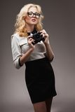 Blonde girl with camera wearing eyeglasses Stock Images