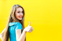 Beautiful blonde girl in blue dress showing finger up. Beautiful blonde girl in blue dress showing finger up, sign OK on a yellow background Stock Images