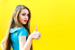 Beautiful blonde girl in blue dress showing finger up. Beautiful blonde girl in blue dress showing finger up, sign OK on a yellow background Royalty Free Stock Photo