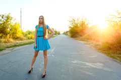Beautiful blonde girl in blue dress standing on a road at sunset. Beautiful blonde girl  with long hair in blue dress standing on a road at sunset background Royalty Free Stock Photos
