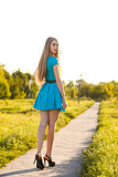 Beautiful blonde girl in blue dress walking on a road in a park. Backlight Royalty Free Stock Image