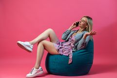 Beautiful blonde girl in a blue jacket and a purple sundress sits on a green bag chair with her legs folded on a pink isolated stock images