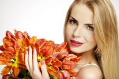 Beautiful blonde girl with the bouquet of tulips isolated on a w Royalty Free Stock Photography