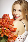 Beautiful blonde girl with the bouquet of tulips isolated on a w Royalty Free Stock Photos