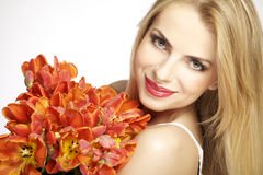 Beautiful blonde girl with the bouquet of tulips isolated on a w Stock Photography