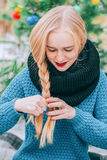 Beautiful blonde girl braids braid, knitted sweater, Winter magic day, the effect retro photo, grain. Beautiful blonde girl braids long braid, knitted sweater Stock Photography