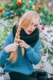 Beautiful blonde girl braids braid, knitted sweater, Winter magic day, the effect retro photo, grain. Beautiful blonde girl braids long braid, knitted sweater Stock Photo