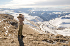 Beautiful blonde girl with a camera to take pictures of Caucasian mountains Stock Image
