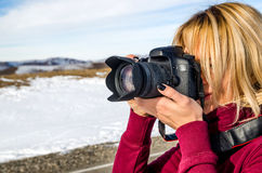Beautiful blonde girl with a camera to take pictures of Caucasian mountains Stock Photos