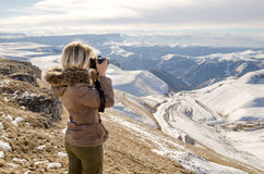 Beautiful blonde girl with a camera to take pictures of Caucasian mountains Stock Images