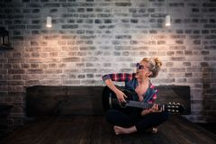 Beautiful blonde girl in causal clothes playing music on guitar and singing royalty free stock photos