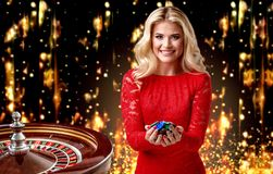 Beautiful blonde girl with chips stands on the background of a royal roulette. collage with a gambler, roulette and