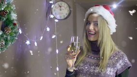 Beautiful blonde girl with Christmas hat holding a glass of champagne on background of Christmas decorations stock video footage