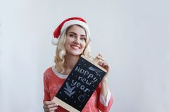 Beautiful blonde girl in a Christmas hat holding a sign with the inscription Happy New Year and smiling stock image
