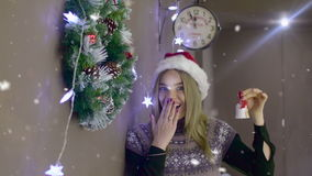 Beautiful blonde girl with Christmas hat ringing a bell on background of Christmas decorations stock video footage