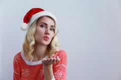 Beautiful blonde girl in Christmas hat sends a kiss stock photo