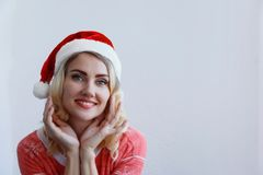 Beautiful blonde girl in christmas hat thinks about christmas and smiling stock photos