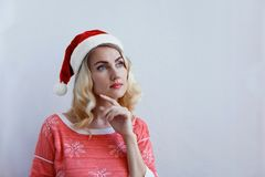 Beautiful blonde girl in christmas hat thinks about christmas and smiling stock image