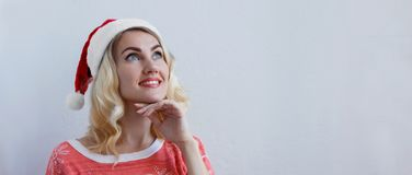 Beautiful blonde girl in christmas hat thinks about christmas and smiling stock images