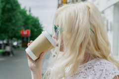 Beautiful blonde girl in the city is drinking coffee. Street photo session. Gray cup with a white lid and a place for the logo royalty free stock image