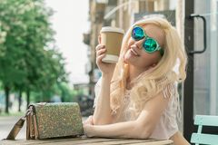 Beautiful blonde girl in the city is drinking coffee. Street photo session. Gray cup with a white lid and a place for the logo royalty free stock images