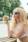 Beautiful blonde girl in the city is drinking coffee. Street photo session. Gray cup with a white lid and a place for the logo stock photography