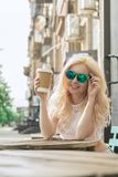 Beautiful blonde girl in the city is drinking coffee. Street photo session. Gray cup with a white lid and a place for the logo stock photos