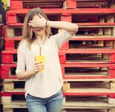 Beautiful blonde girl closes her eyes stands near the wooden racks. Outdoor Royalty Free Stock Photos
