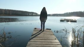 A beautiful blonde girl in a coat is walking on a pier by the lake. On the lake, autumn and cloudy mood stock footage