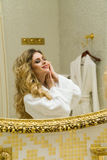 Beautiful blonde girl corrects her hair and looking in the mirror in her bathroom. Beauty young woman corrects her hair stock images