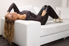 Beautiful blonde girl on the couch. Beautiful blond woman lying on a white couch, she is dressed in leggings, shirt and shoes in the heel, interior photos Stock Photos
