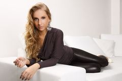 Beautiful blonde girl on the couch. Beautiful blond woman lying on a white couch, she is dressed in leggings, shirt and shoes in the heel, interior photos Stock Images