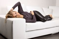 Beautiful blonde girl on the couch. Beautiful blond woman lying on a white couch, she is dressed in leggings, shirt and shoes in the heel, interior photos Royalty Free Stock Photography