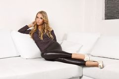 Beautiful blonde girl on the couch. Beautiful blond woman lying on a white couch, she is dressed in leggings, shirt and shoes in the heel, interior photos Royalty Free Stock Image