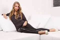 Beautiful blonde girl on the couch. Beautiful blond woman lying on a white couch, she is dressed in leggings, shirt and shoes in the heel, interior photos Stock Photography