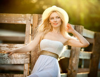 Beautiful blonde girl with country look near an old wooden fence in sunny summer day. Attractive woman with white hat and dress, American country style farmer royalty free stock image