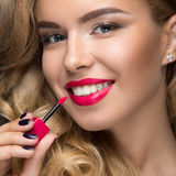 Beautiful blonde girl with curls, red lips and a smile on her face. Stock Photo