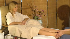Beautiful blonde girl doing foot massage. Therapeutic massage. stock video footage