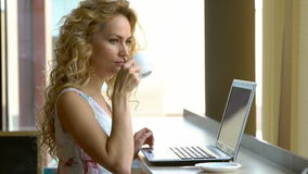 Beautiful blonde girl in dress using laptop in cafe. Young woman drinks coffee and working on notebook. Blogger work concept stock footage