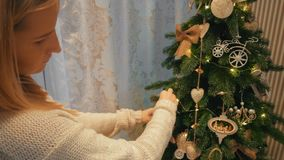 Beautiful blonde girl dresses up a Christmas tree in a cozy evening house stock footage