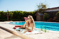Beautiful blonde girl drinking cocktail, sunbathing, lying near swimming pool. Stock Photography